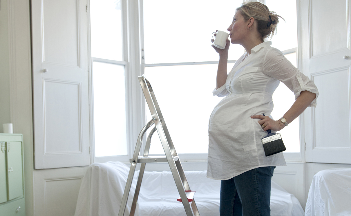 Pregnant woman taking a break during decorating holding a brush with stepladder and paint pots